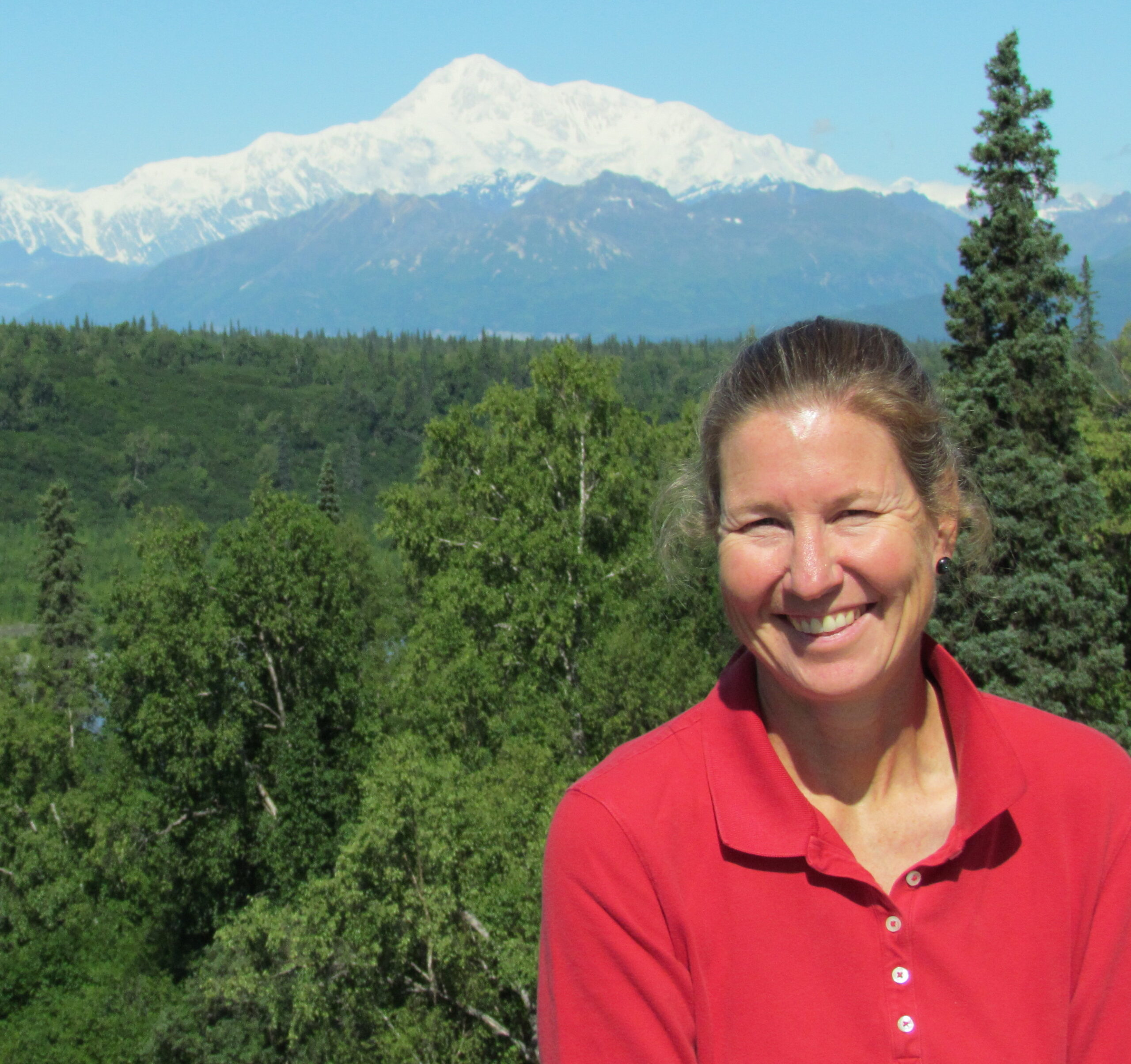 Betsy wearing red shirt smiling with forest and Denali mountain in the background